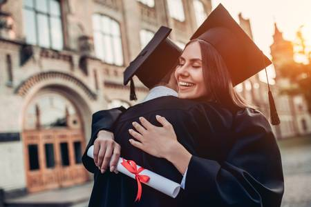 83757000-graduates-in-mantles-with-diplomas-in-hands-are-standing-near-university-and-hugging-each-other- (1).jpg
